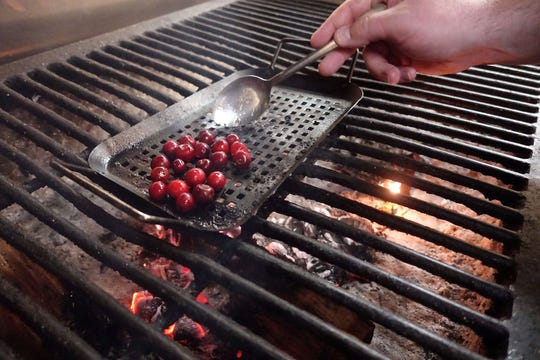 Cullen Campbell grills sour cherries at Crudo in Phoenix.