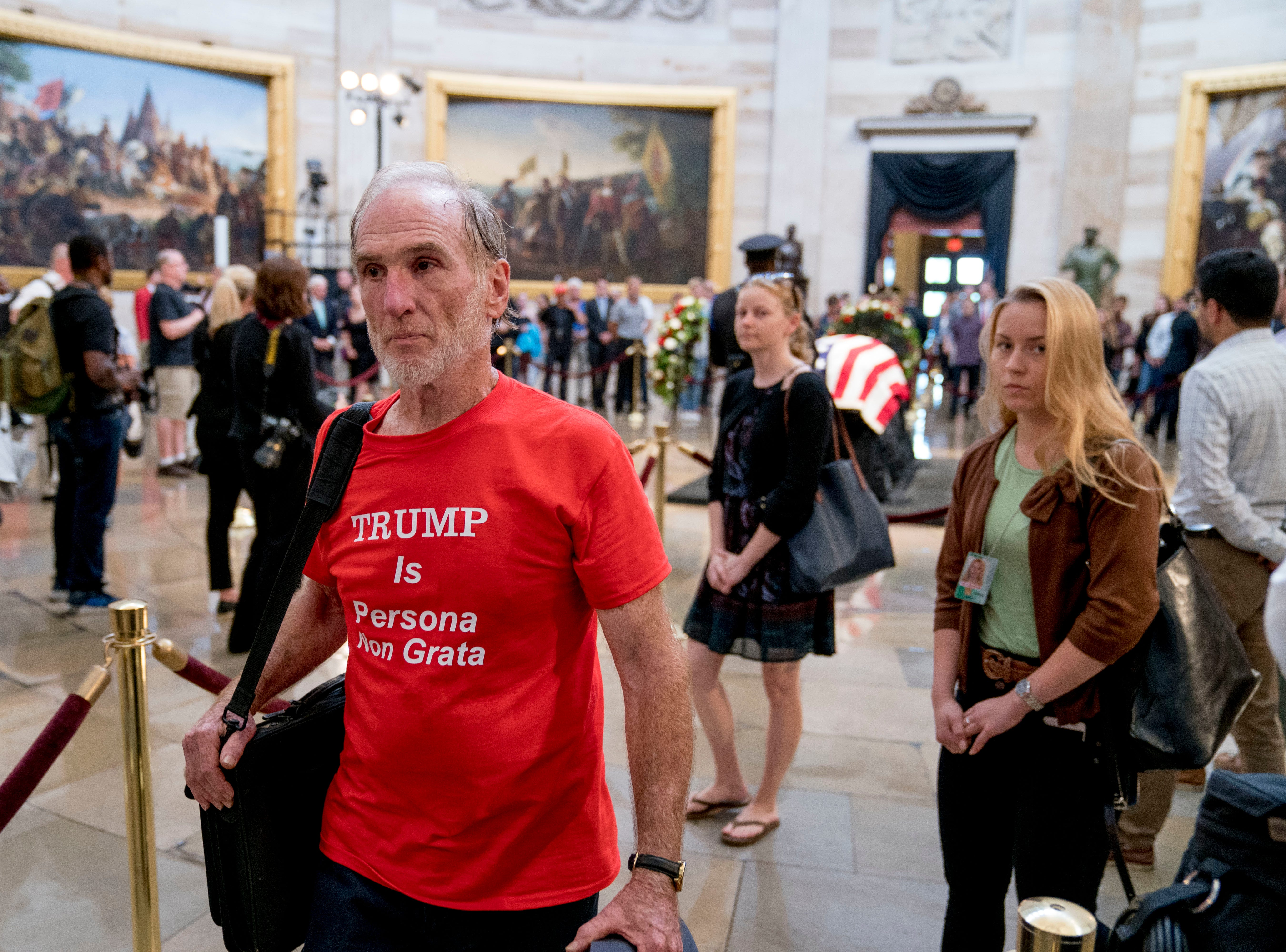 "A man wearing a shirt that reads ""Trump is Persona Non Grata"" walks through the Rotunda as Sen. John McCain, R-Ariz., lies in state in the U.S. Capitol, Friday, Aug. 31, 2018, in Washington. (AP Photo/Andrew Harnik)"