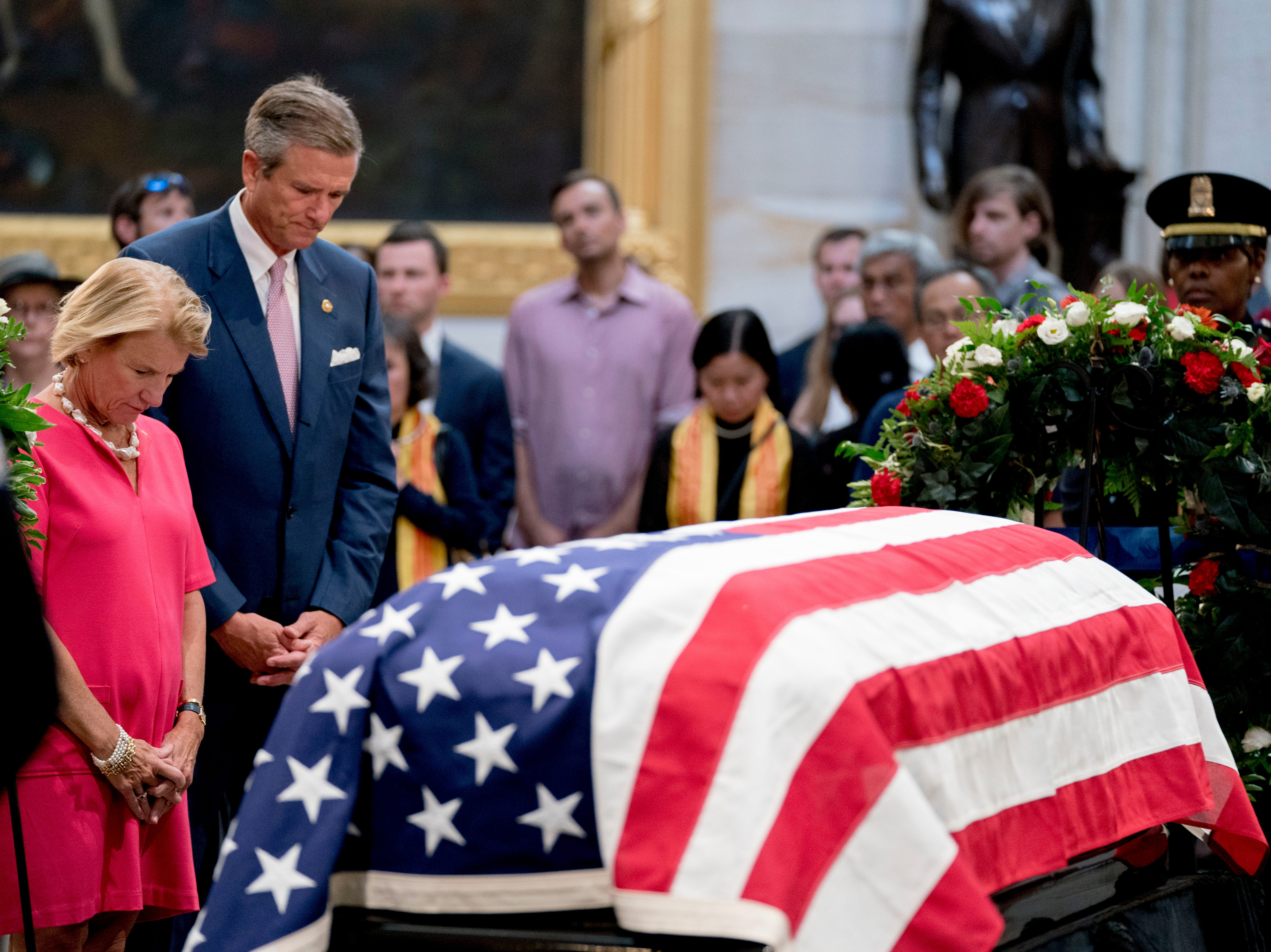 Sen. Shelley Moore Capito, R-W.Va., left, and her husband Charles Capito pay their respects to Sen. John McCain, R-Ariz., as he lies in state in the Rotunda of the U.S. Capitol, Friday, Aug. 31, 2018, in Washington. (AP Photo/Andrew Harnik)