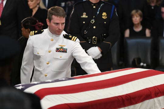 Jack McCain touches his father's casket as the body of John McCain lies in state at the U.S. Capitol in Washington on Aug. 31, 2018 in Washington.