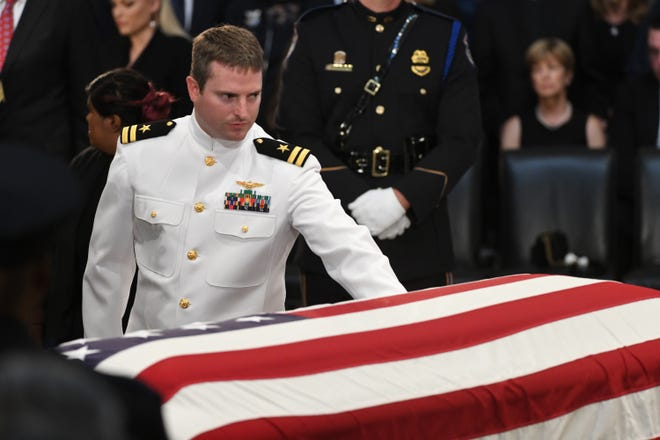 Jack McCain touches his father's casket as the body of John McCain lies in state at the U.S. Capitol in Washington on Aug. 31, 2018, in Washington. Sen. McCain died on Aug. 25.