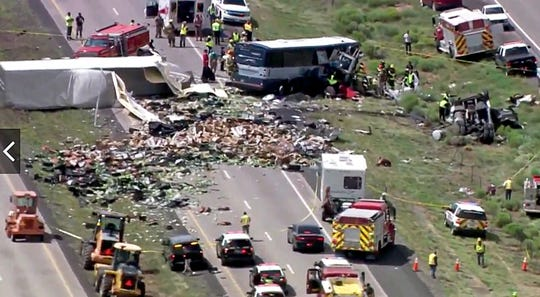 This photo from video provided by KQRENews13 shows first responders working the scene of a deadly collision between a Greyhound passenger bus and a semi-truck on Interstate 40 near the town of Thoreau, N.M., near the Arizona border, Thursday, Aug. 30, 2018. Multiple people were killed and others were seriously injured. Officers and rescue workers were on scene but did not provide details about how many people were killed or injured, or what caused the crash. (KQRENews13 via AP)