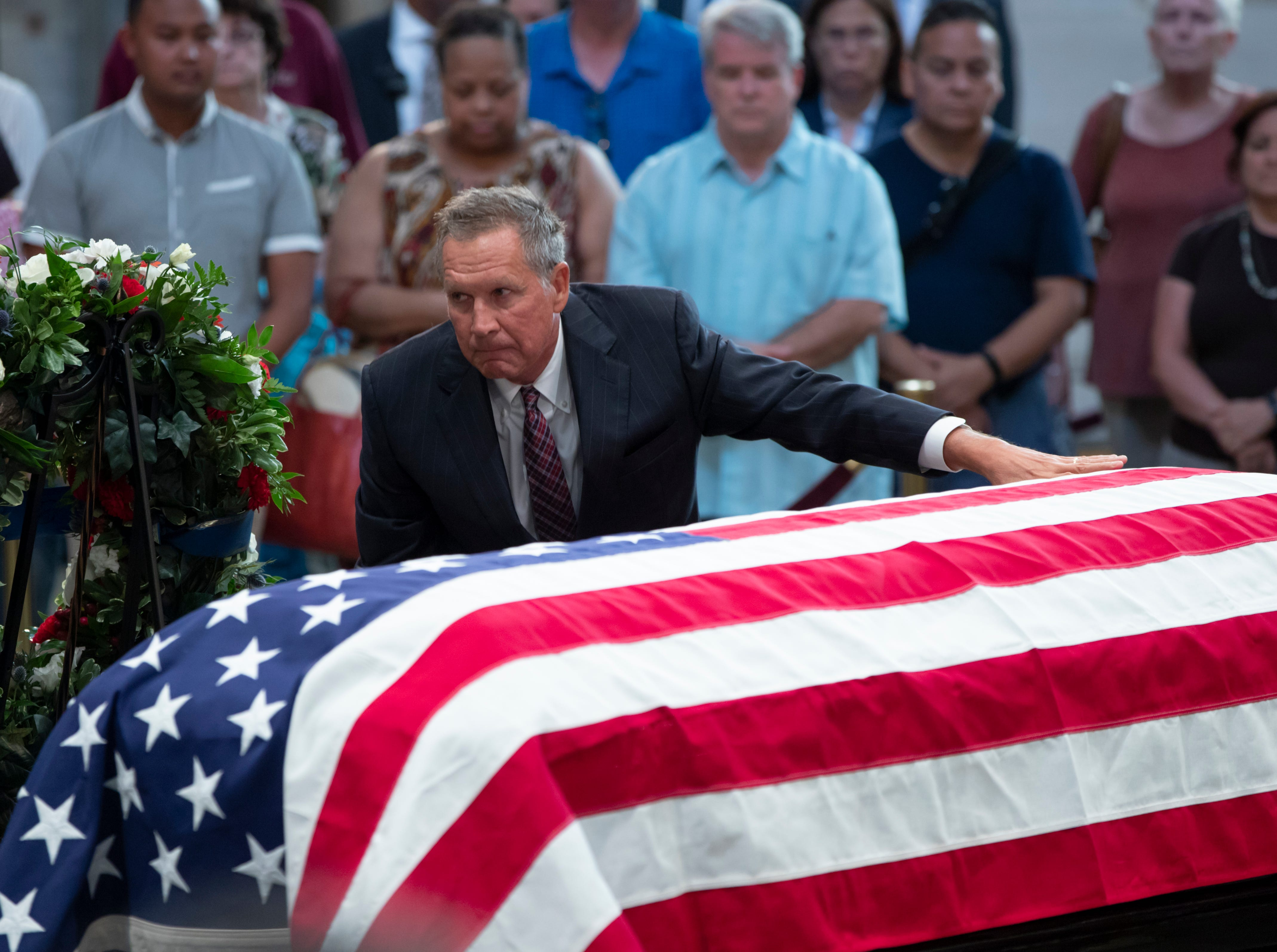 Ohio Gov. John Kasich kneels at the flag-draped casket of Sen. John McCain of Arizona, who lived and worked in Congress over four decades, in the U.S. Capitol rotunda, Friday, Aug. 31, 2018, in Washington. McCain was a six-term senator, a former Republican nominee for president, and a Navy pilot who served in Vietnam, where he endured five-and-a-half years as a prisoner of war. He died Aug. 25 from brain cancer at age 81. (AP Photo/J. Scott Applewhite)