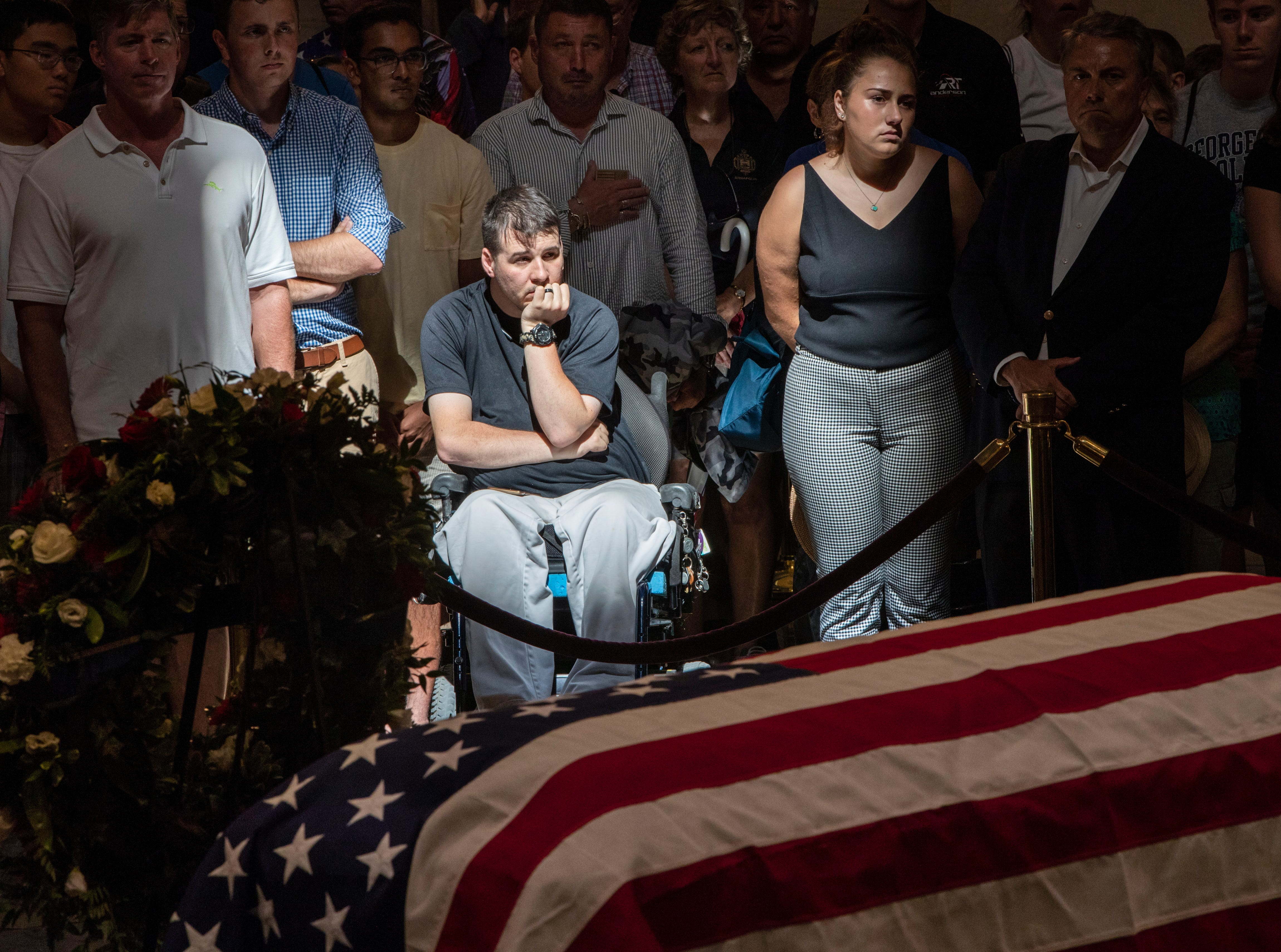 Derek Anderson (center) of Arlington, Virginia, pays his respects with other members of the public at the flag-draped casket of Sen. John McCain of Arizona in the U.S. Capitol rotunda in Washington Aug. 31, 2018.