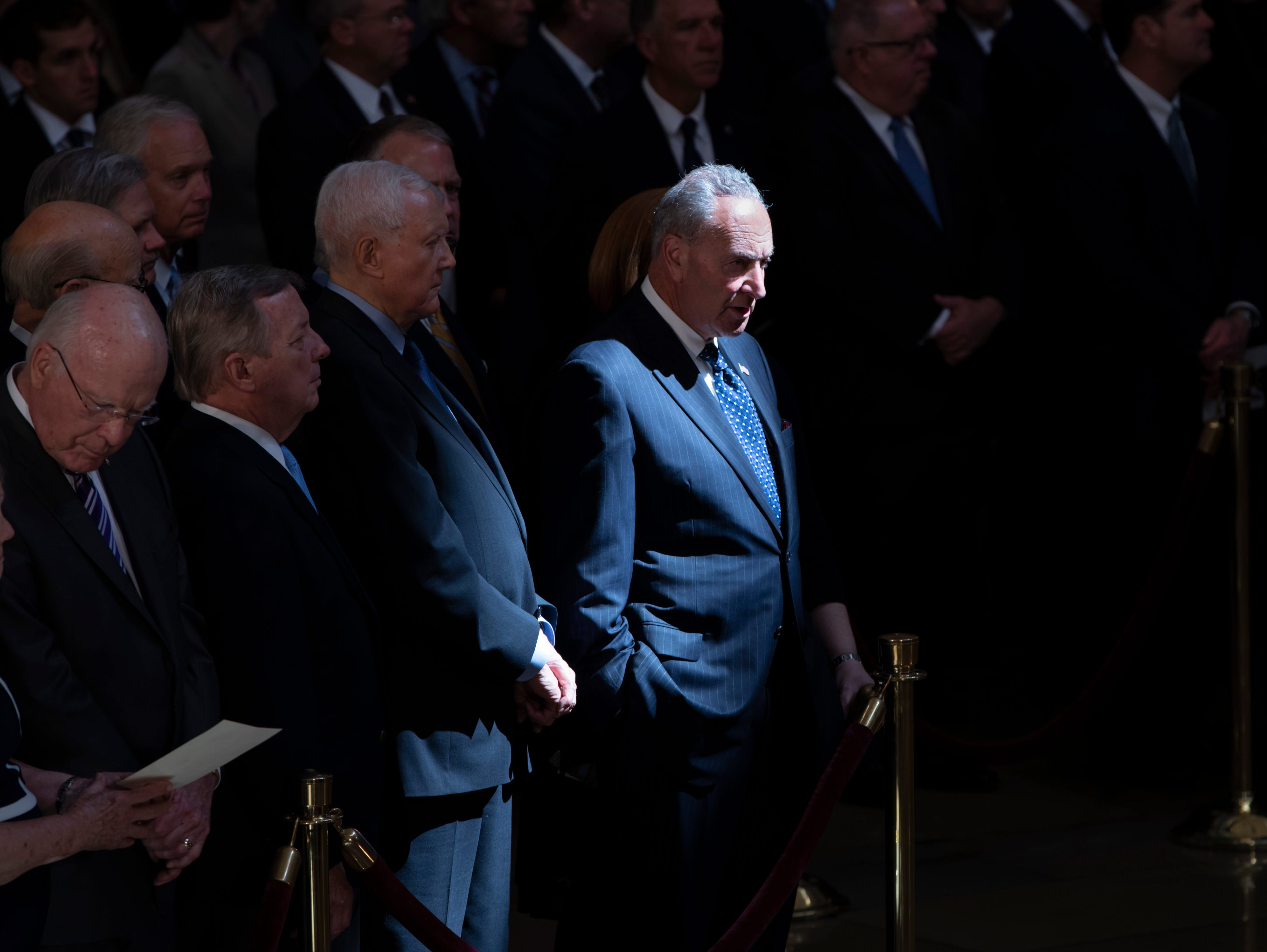 Senate Minority Leader Chuck Schumer, D-N.Y., center, and other members of the Senate, stand as the flag-draped casket bearing the remains of Sen. John McCain of Arizona, lies in state in the U.S. Capitol rotunda for a farewell ceremony and public visitation, Friday, Aug. 31, 2018, in Washington. (AP Photo/J. Scott Applewhite)