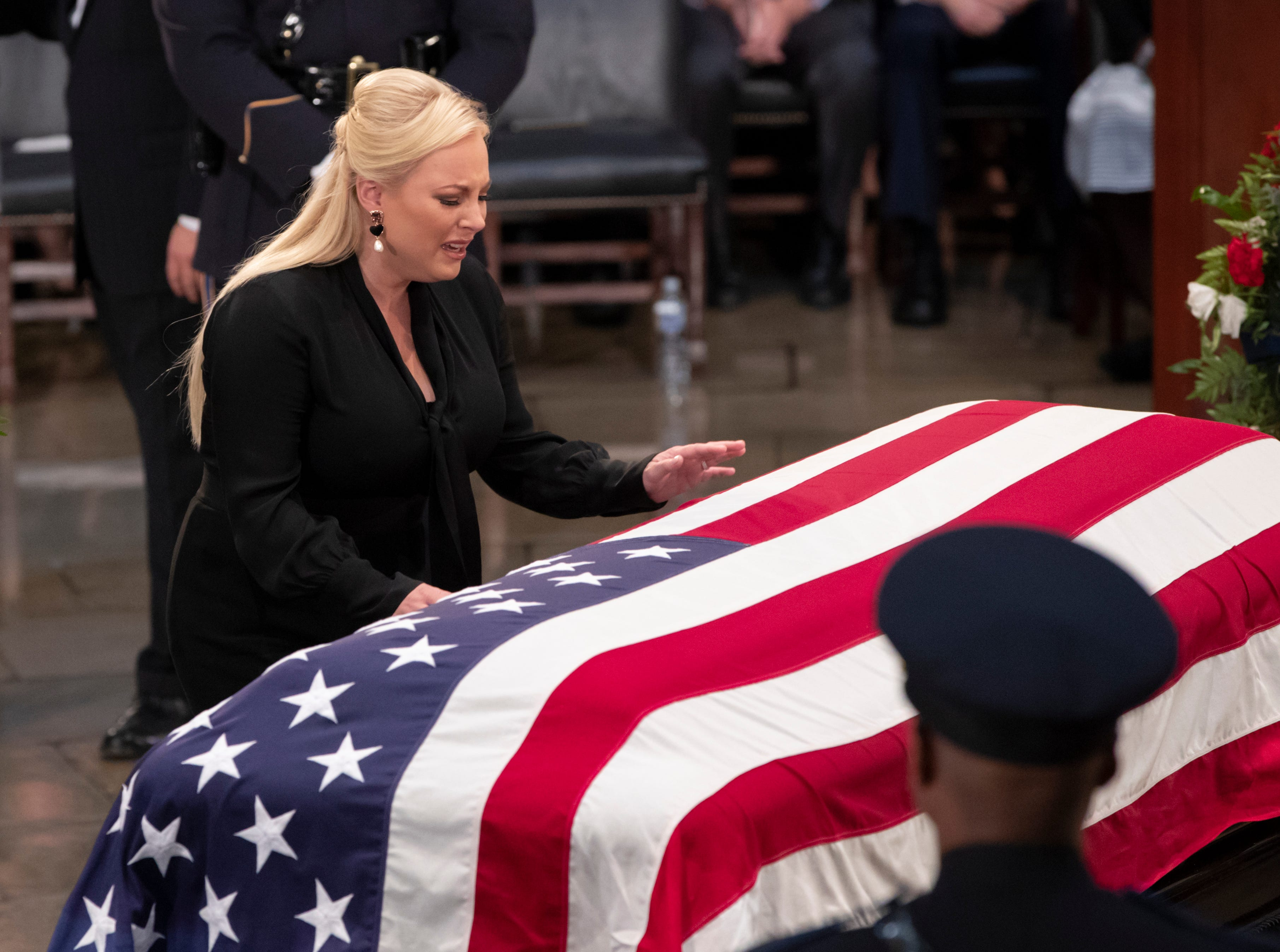 Meghan McCain reaches out to touch the flag-draped casket bearing the remains of her father, Sen. John McCain, R-Ariz., during a farewell ceremony in the Capitol Rotunda, Friday, Aug. 31, 2018, in Washington.  (AP Photo/J. Scott Applewhite)