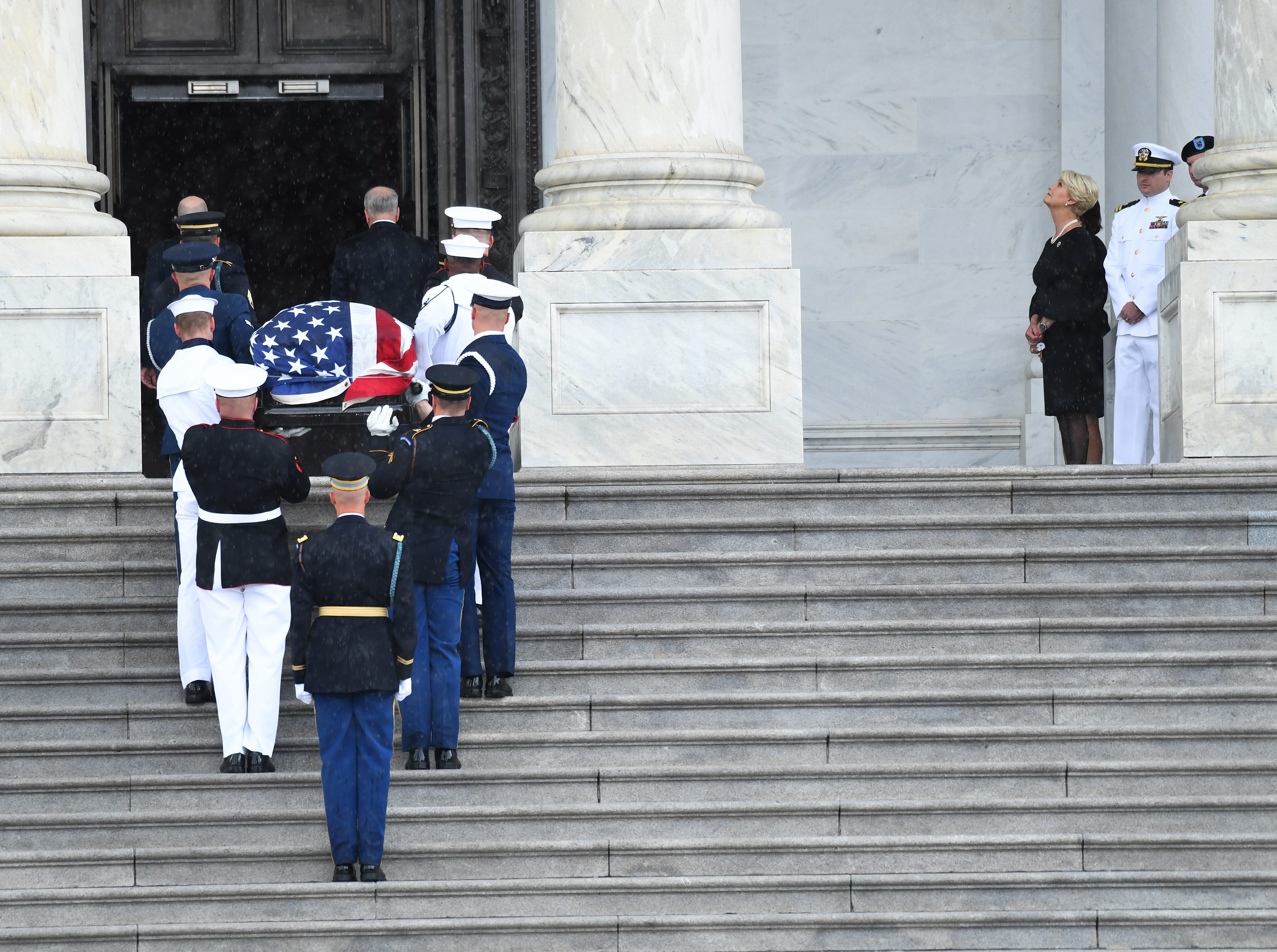 The casket of Sen. John McCain arrives at the U.S. Capitol while his wife, Cindy McCain, looks skyward and their two sons Jack and Jimmy McCain look on on Aug. 31, 2018.