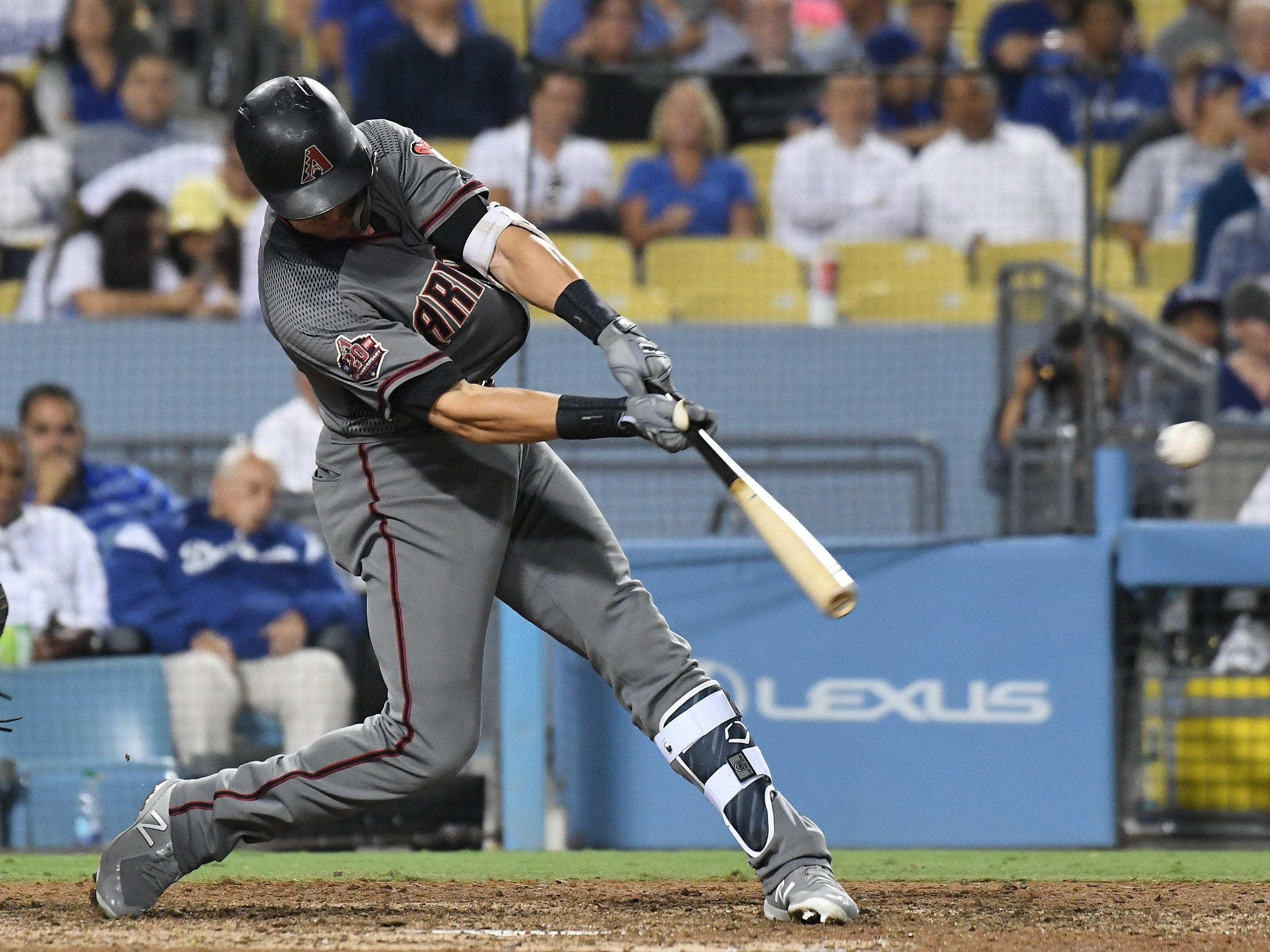 Aug 30, 2018; Los Angeles, CA, USA; Arizona Diamondbacks shortstop Nick Ahmed (13) hits a single against the Los Angeles Dodgers in the eighth inning at Dodger Stadium. Mandatory Credit: Richard Mackson-USA TODAY Sports