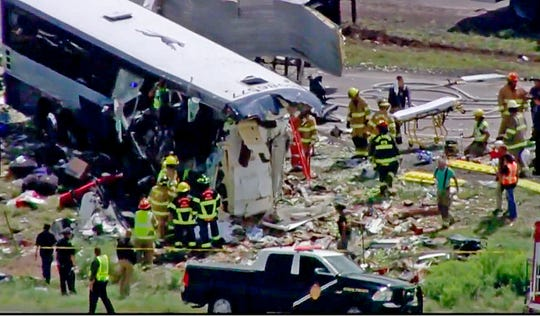 This photo from video provided by KQRENews13 shows first responders working the scene of a collision between a Greyhound passenger bus and a semitruck on Interstate 40 near the town of Thoreau, N.M., on Aug. 30, 2018.