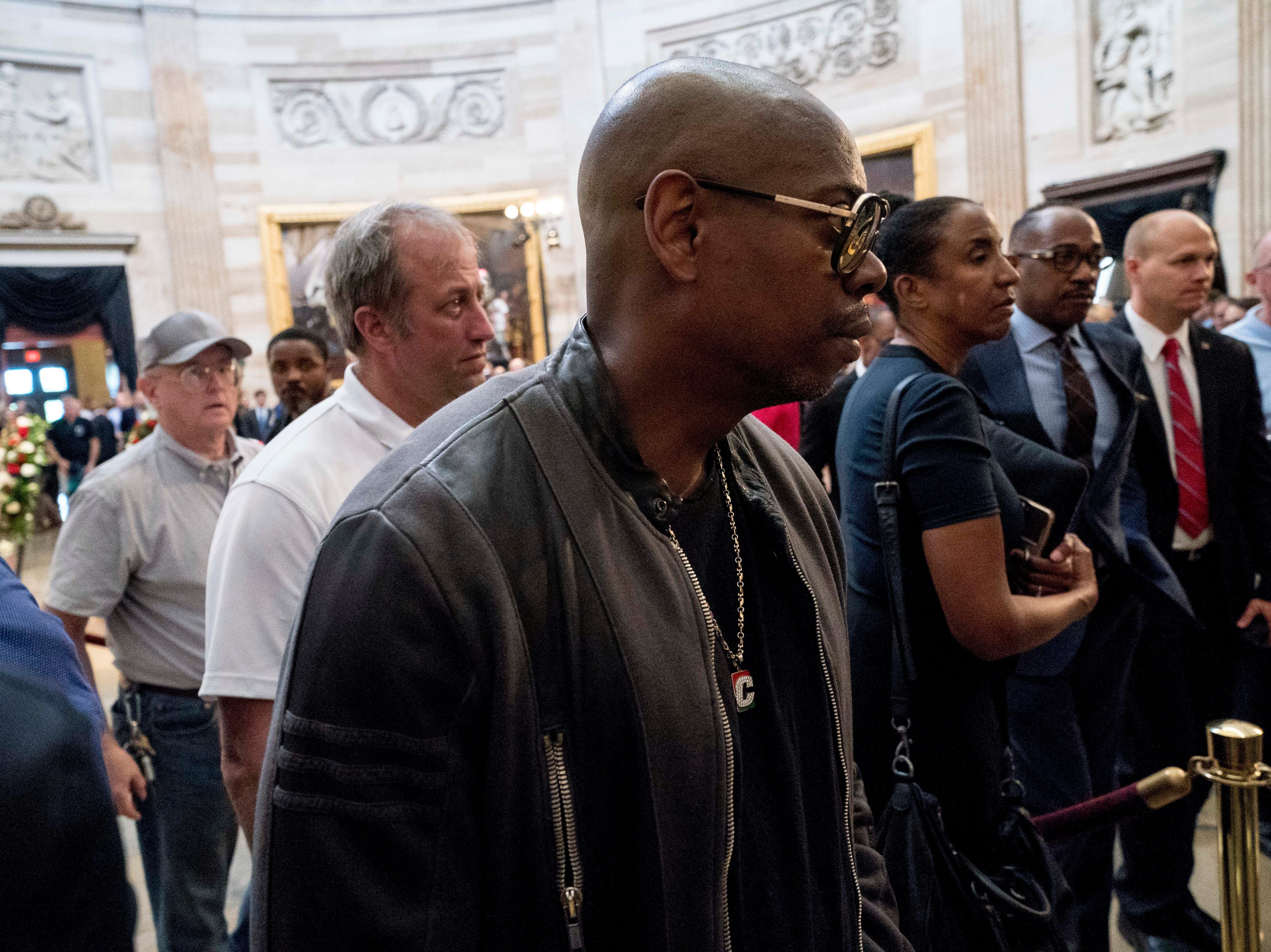 Comedian Dave Chappelle walks through the rotunda as Sen. John McCain, R-Ariz., lies in state at the U.S. Capitol Aug. 31, 2018, in Washington.