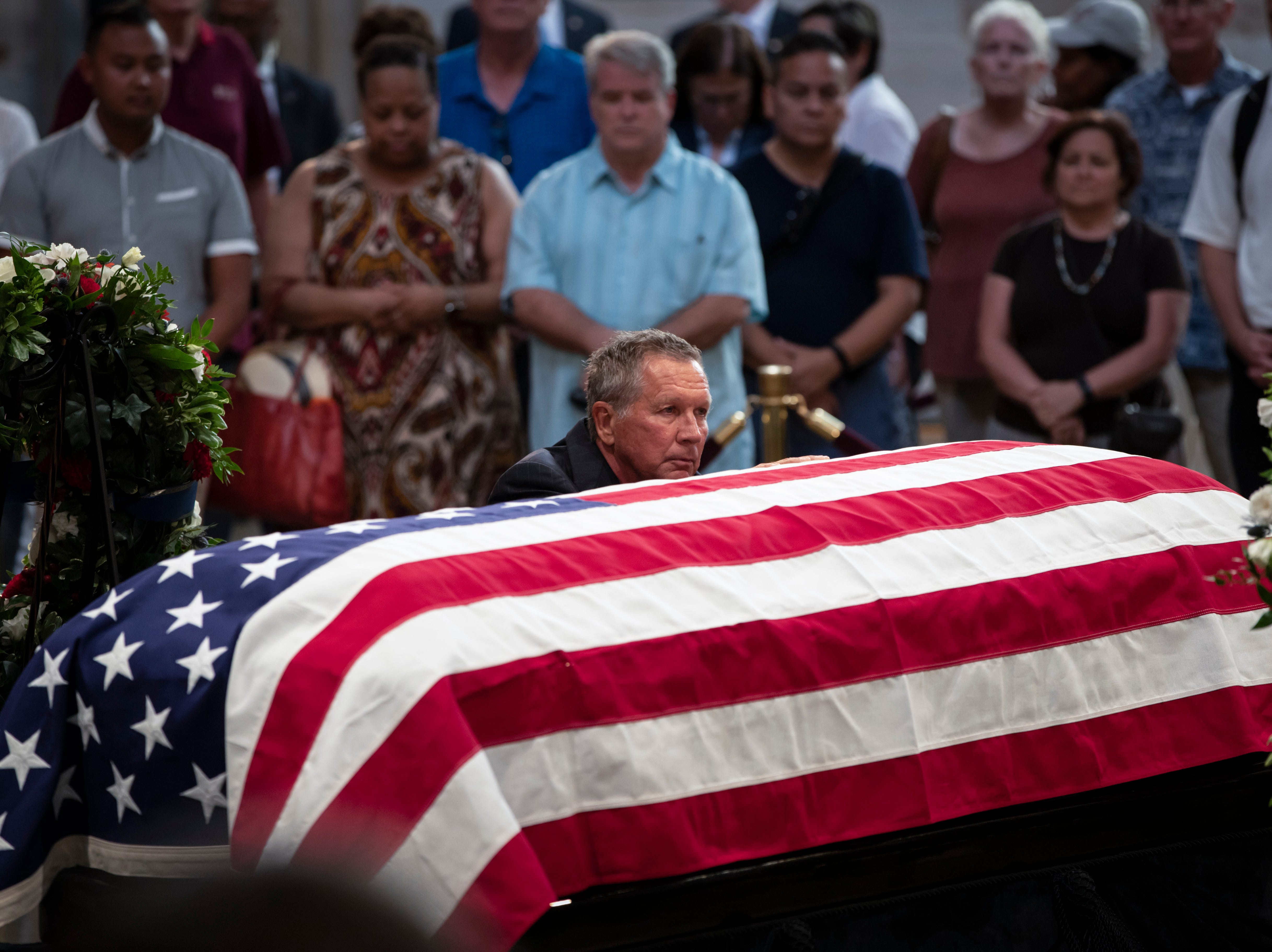 Ohio Gov. John Kasich kneels at the flag-draped casket of Sen. John McCain of Arizona, who lived and worked in Congress over four decades, in the U.S. Capitol rotunda, Friday, Aug. 31, 2018, in Washington. (AP Photo/J. Scott Applewhite)