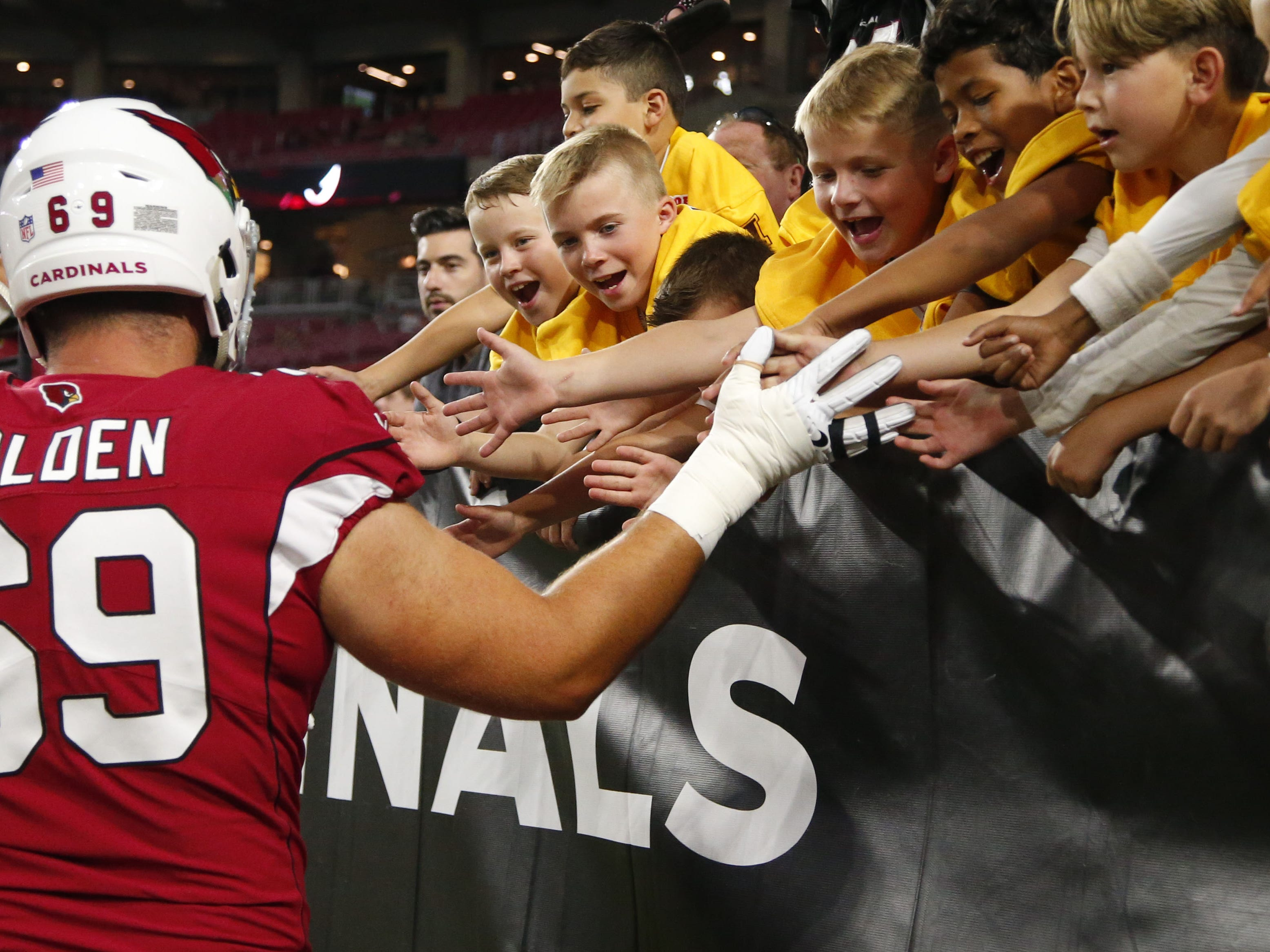 Arizona Cardinals offensive tackle Will Holden (69) high fives the players from the Hombres Pop Warner football team before a NFL game against the Denver Broncos at the University of Phoenix Stadium in Glendale on August 30, 2018.