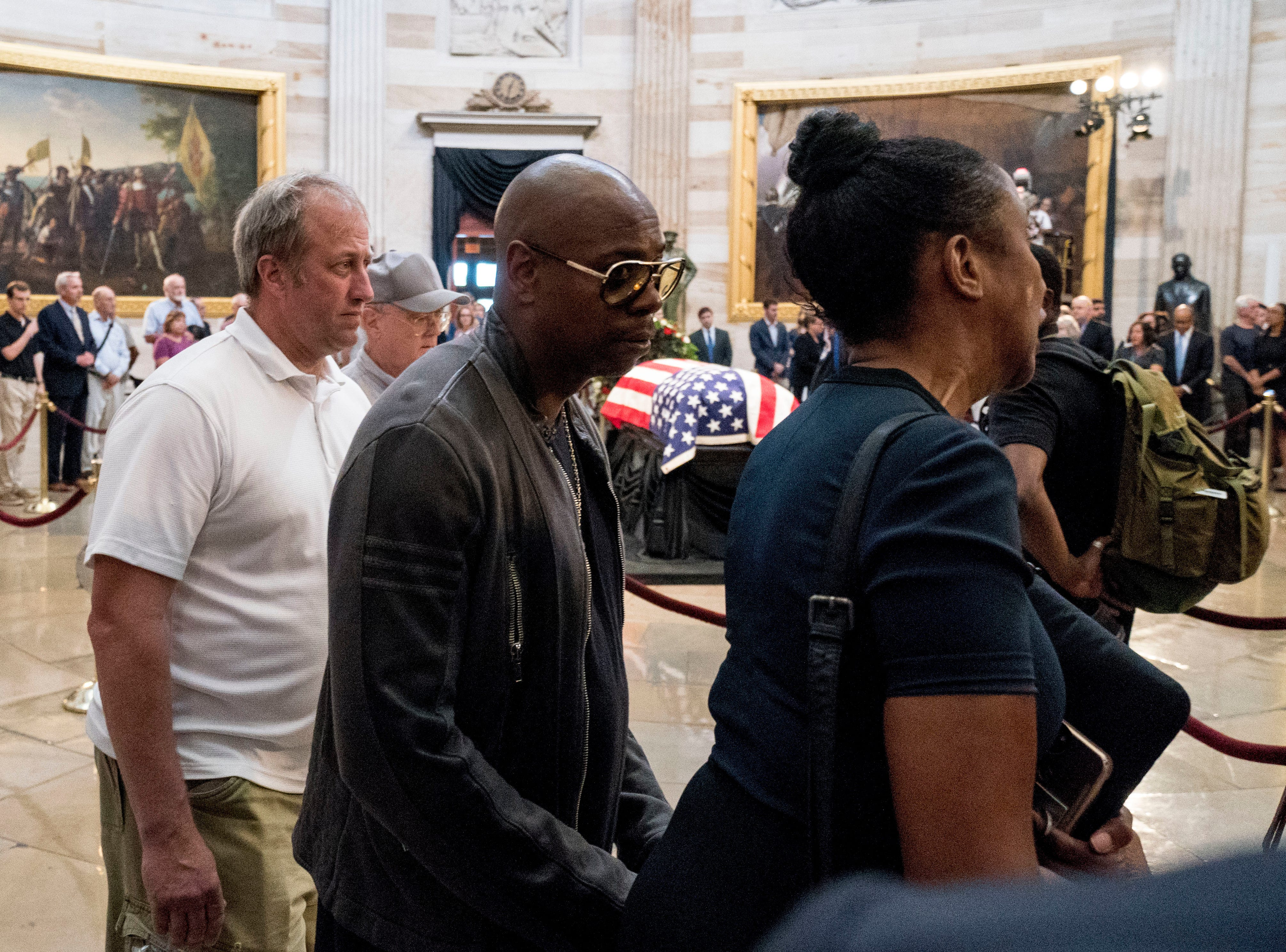 Comedian Dave Chappelle, center, walks through the Rotunda as Sen. John McCain, R-Ariz., lies in state at the U.S. Capitol, Friday, Aug. 31, 2018, in Washington. (AP Photo/Andrew Harnik)