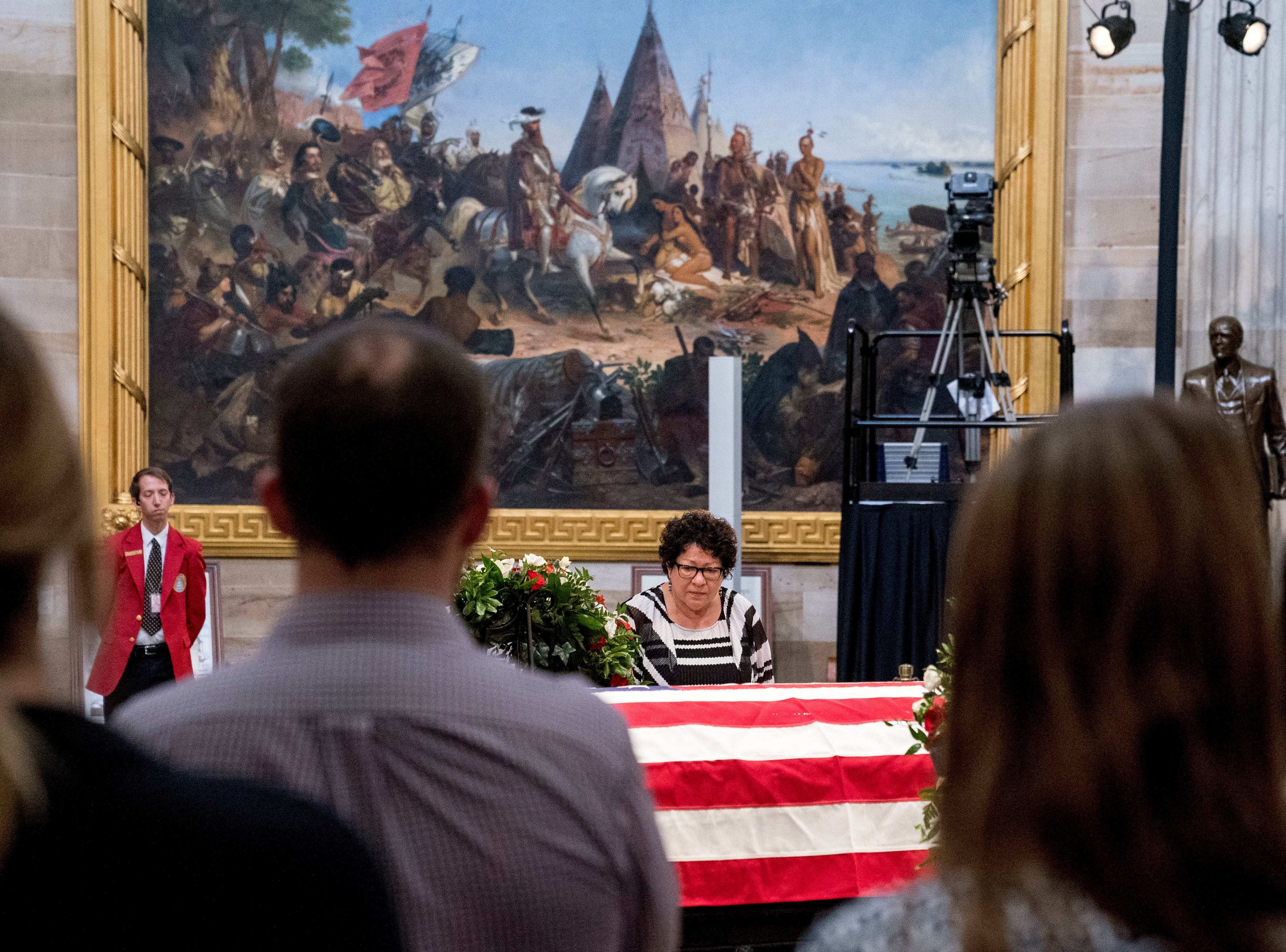 Members of the public watch as Supreme Court Justice Sonia Sotomayor stands over the casket of Sen. John McCain, R-Ariz., as he lies in state in the Rotunda of the U.S. Capitol, Friday, Aug. 31, 2018, in Washington. (AP Photo/Andrew Harnik)