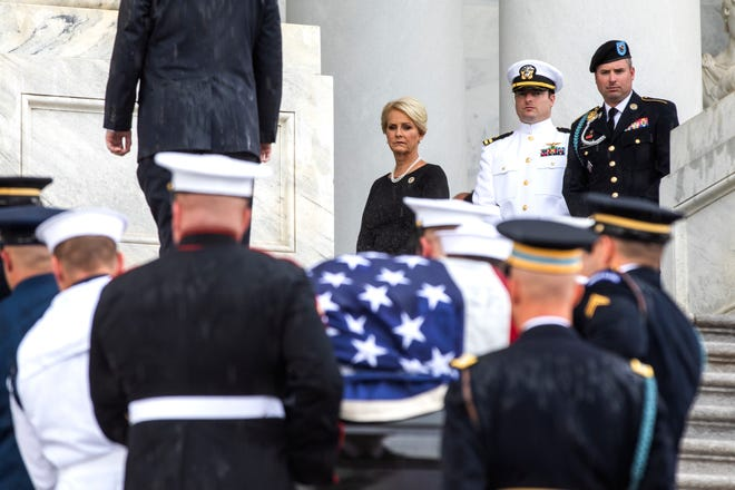 The flag-draped casket of Sen. John McCain, R-Ariz., is carried up the steps of the U.S. Capitol Aug. 31, 2018, in Washington as Cindy McCain, top right, joined by her sons Jack McCain, and James McCain, look on.