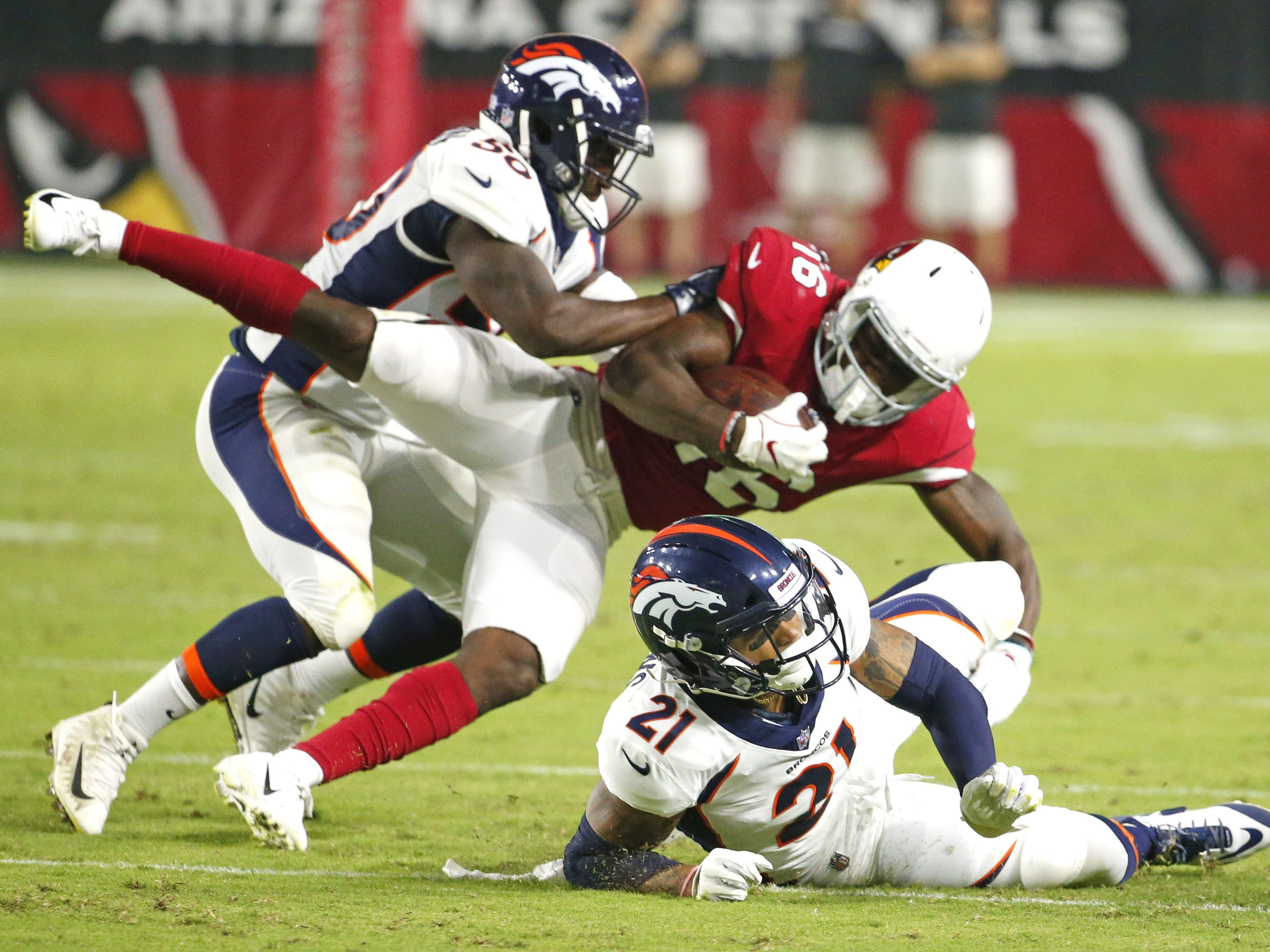 Denver Broncos linebacker Zaire Anderson (50) and defensive back Su'a Cravens (21) tackle Arizona Cardinals wide receiver Trent Sherfield (16)during a NFL game at the University of Phoenix Stadium in Glendale on August 30, 2018.