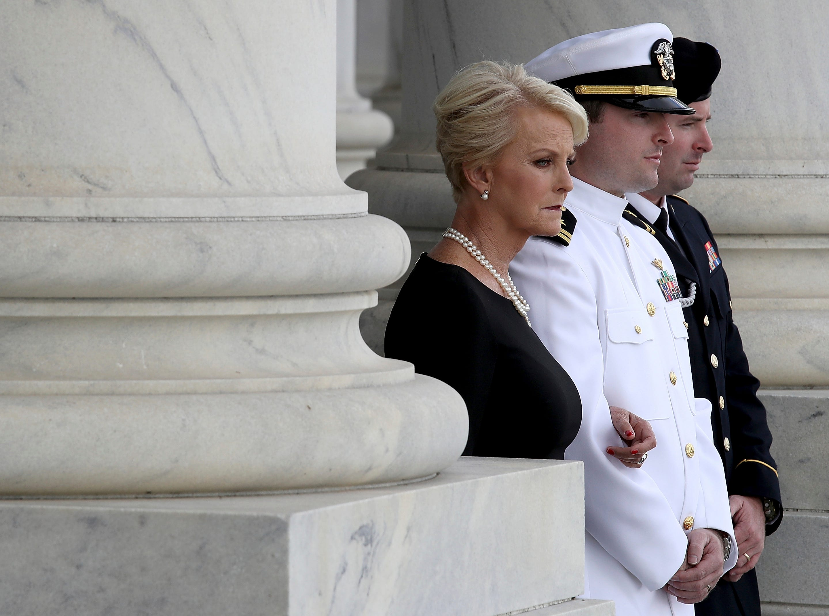Cindy McCain, Jack McCain, and James McCain watch as a military honor guard team carries the casket of Sen. John McCain, R-Ariz., into the U.S. Capitol Aug. 31, 2018.