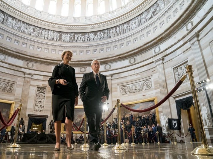 Senate Majority Leader Mitch McConnell  of Kentucky, accompanied by an aide, walks through the rotunda before the casket of Sen. John McCain, R-Ariz., lies in state at the U.S. Capitol Aug. 31, 2018.