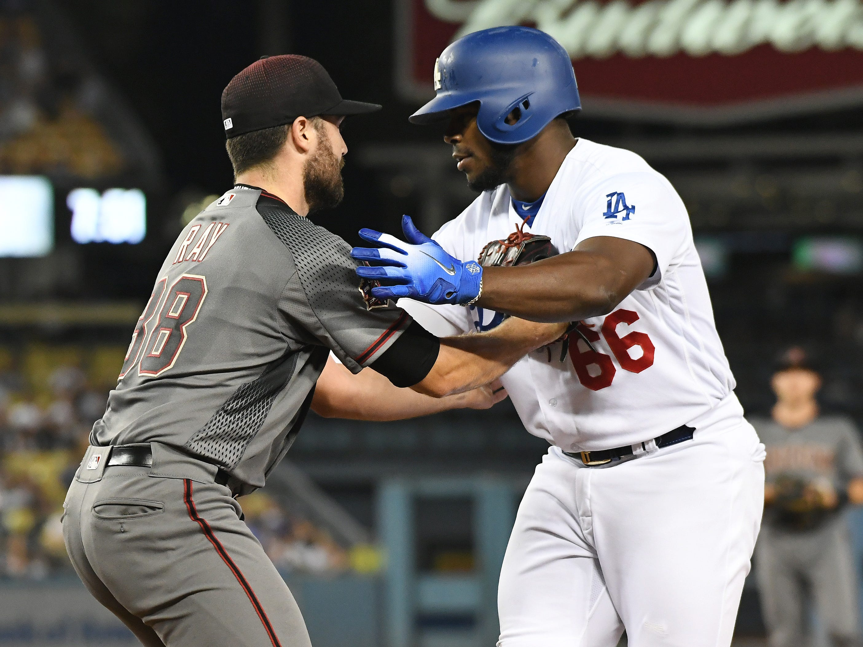 Aug 30, 2018; Los Angeles, CA, USA; Arizona Diamondbacks starting pitcher Robbie Ray (38) tags out Los Angeles Dodgers right fielder Yasiel Puig (66) at first base in the second inning at Dodger Stadium. Mandatory Credit: Richard Mackson-USA TODAY Sports