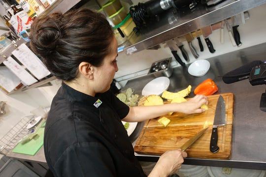 Danielle Leoni chops pineapple for a dish at The Breadfruit & Rum Bar in Phoenix.