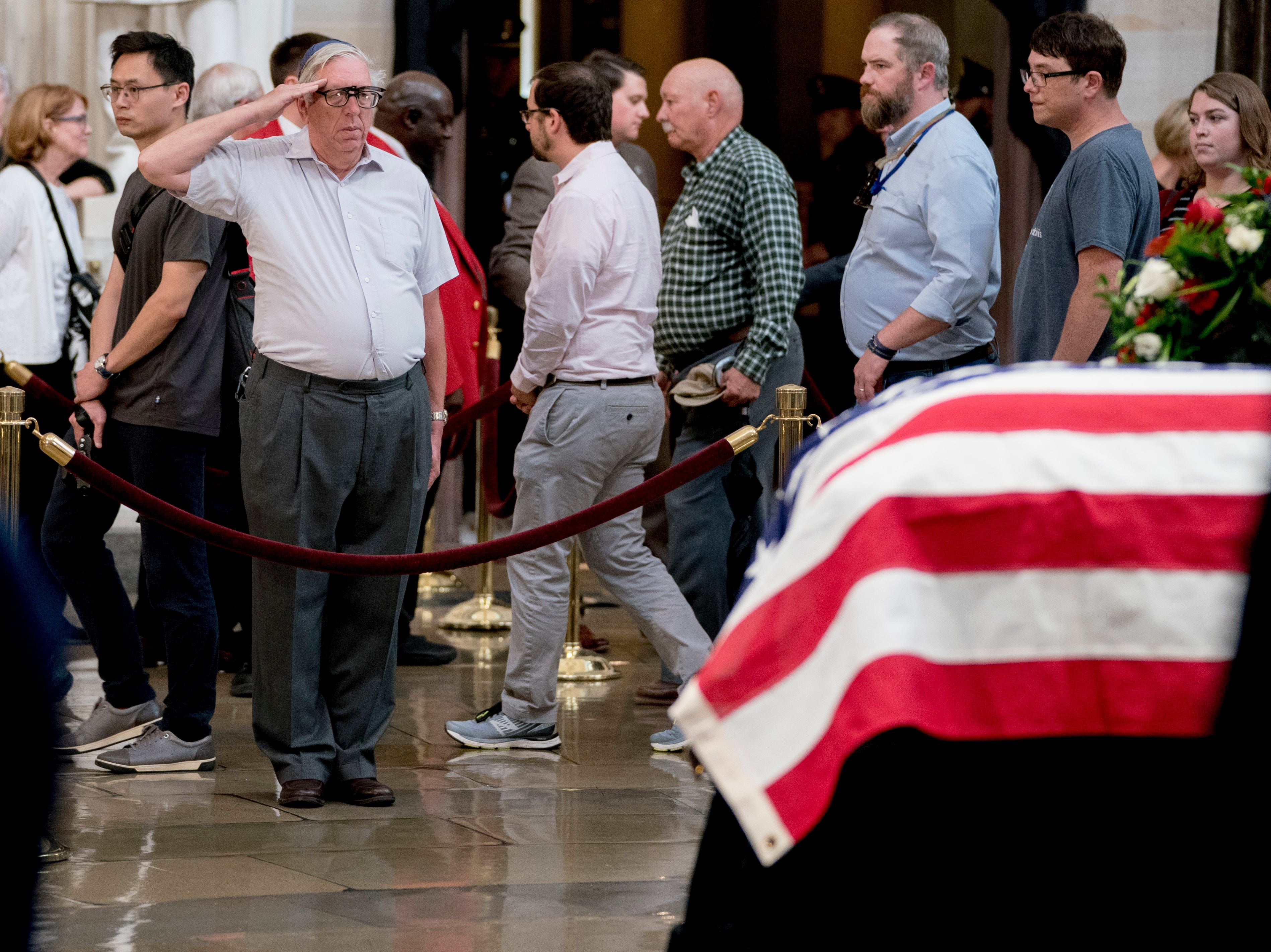 A visitor salutes the casket of Sen. John McCain, R-Ariz., as he lies in state in the Rotunda of the U.S. Capitol, Friday, Aug. 31, 2018, in Washington. (AP Photo/Andrew Harnik)