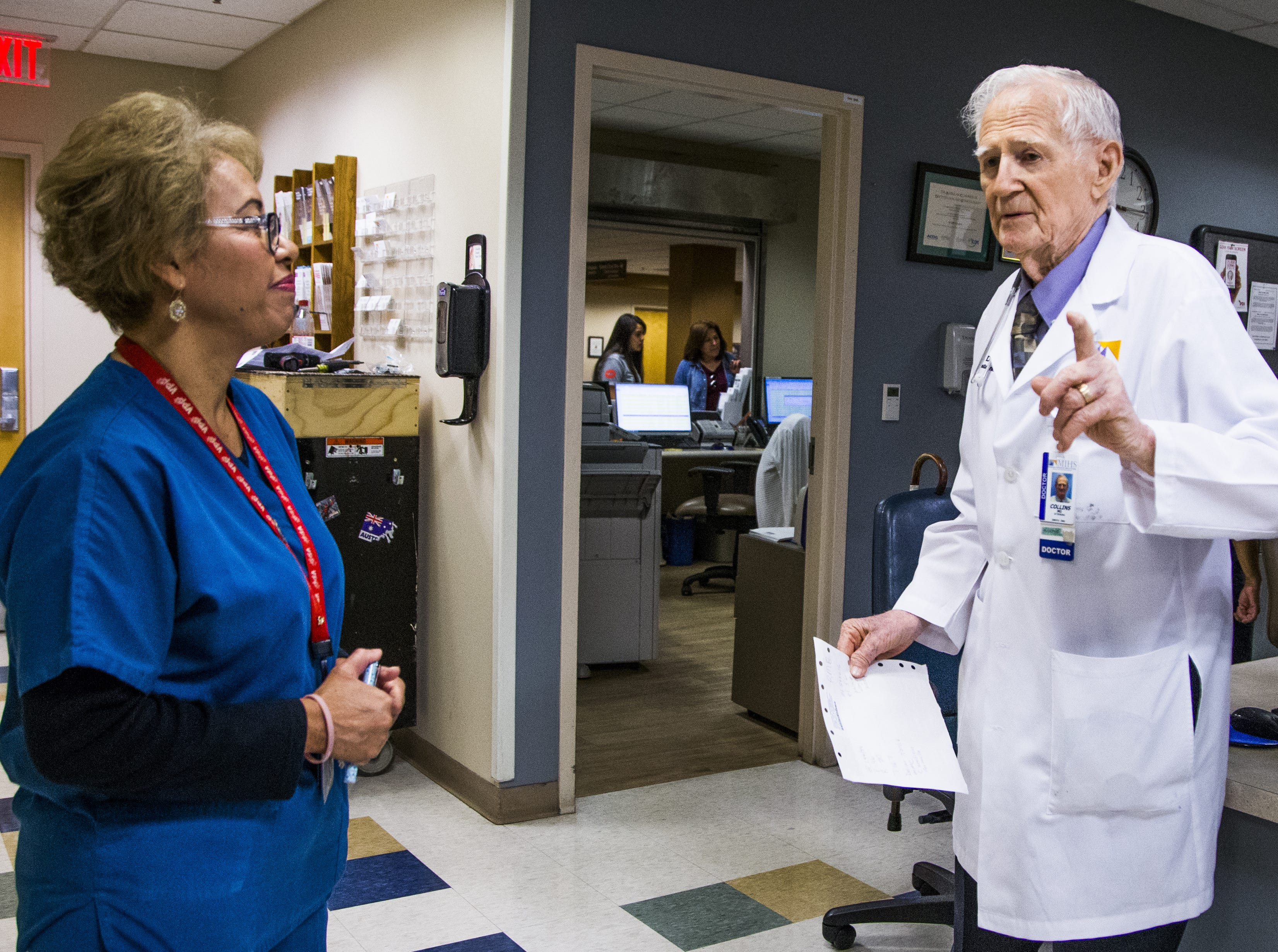 Dr. C. Dale Collins, 98, is finally retiring. He chats with medical assistant Isabel Gonzalez, left, on Aug. 24, 2018, one of his last days at Maricopa Integrated Health System.