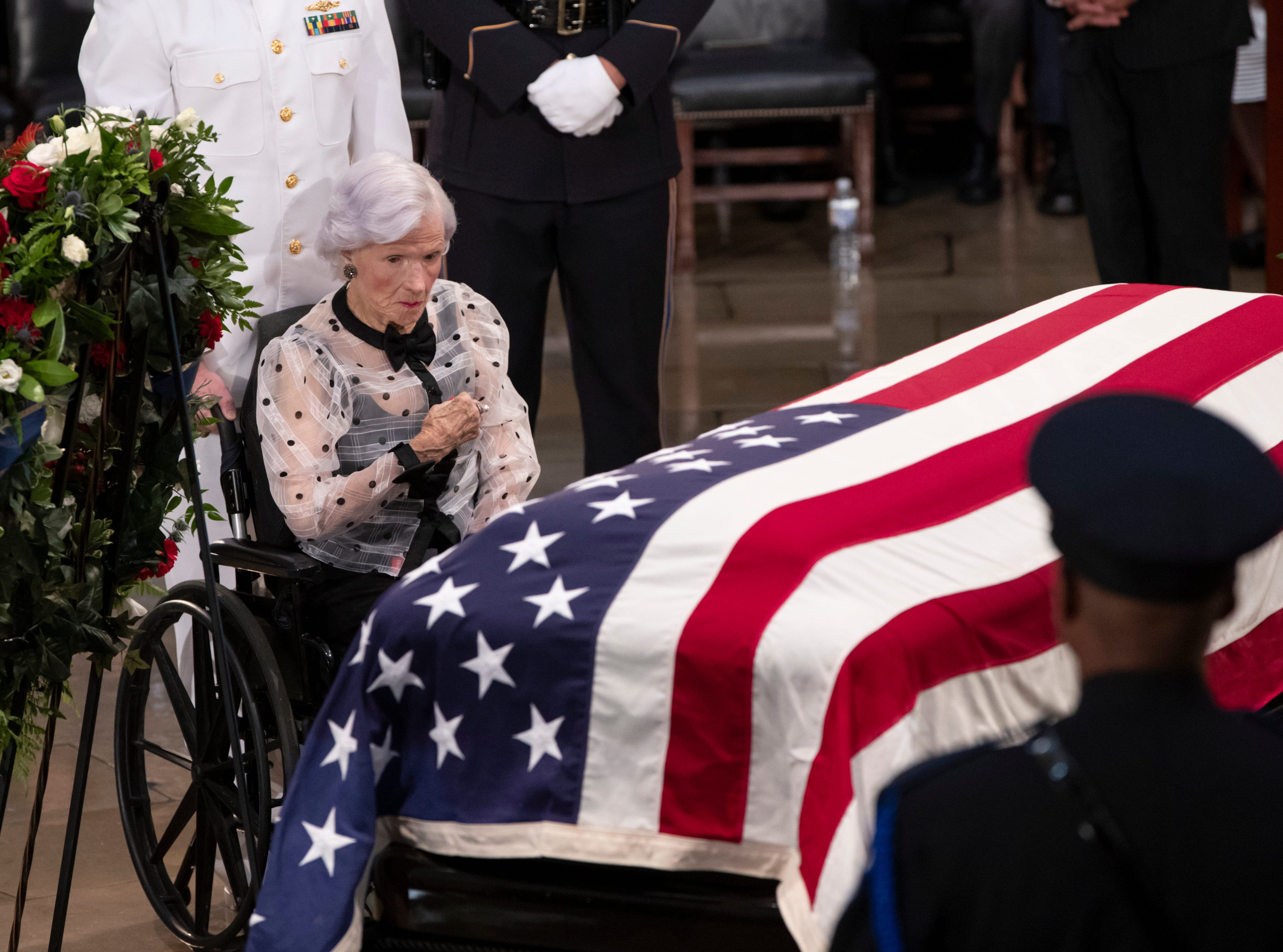 Roberta McCain, the 106-year-old mother of Sen. John McCain of Arizona, stops at his flag-draped casket in the U.S. Capitol rotunda during a farewell ceremony, Friday, Aug. 31, 2018, in Washington. (AP Photo/J. Scott Applewhite)