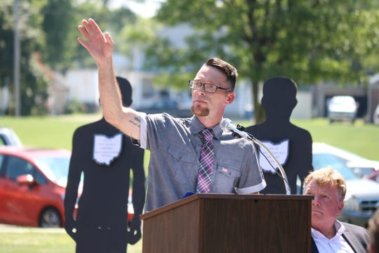Jeffery Schill, a graduate of Ottawa County's Drug Court, said his recovery is a product of local programs offered to help addicts receive treatment. In the background are silhouettes representing overdose deaths in Ottawa County in 2017.