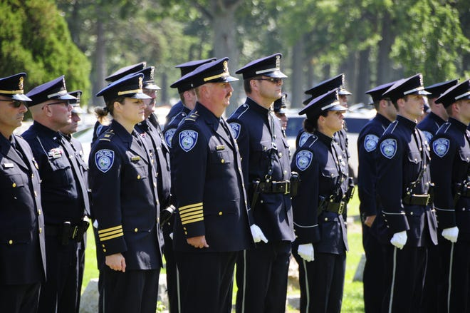 Port Huron officers including Capt. Marcy Kuehn and Chief Joseph Platzer stand to attention at the funeral service for Lt. Joel Wood on Friday, Aug. 31, 2018