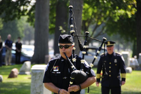 James Disser, a detective from the Marysville Police Department serving in the Major Crimes Unit, plays bagpipes at Lakeside Cemetery during services for Lt. Joel Wood.