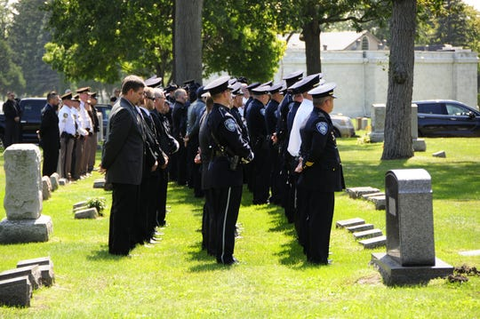 Police officers stand in a body during graveside services for Lt. Joel Wood at Lakeside Cemetery on Friday, Aug. 31, 2018