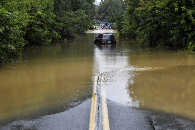A car is stuck in water as Freysville Road in Hellam Township, was flooded Friday.