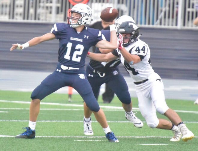 South Western's Ryan Sheehan moves in to grab the throwing arm of Chambersburg quarterback Brady Stumbaugh Friday night.