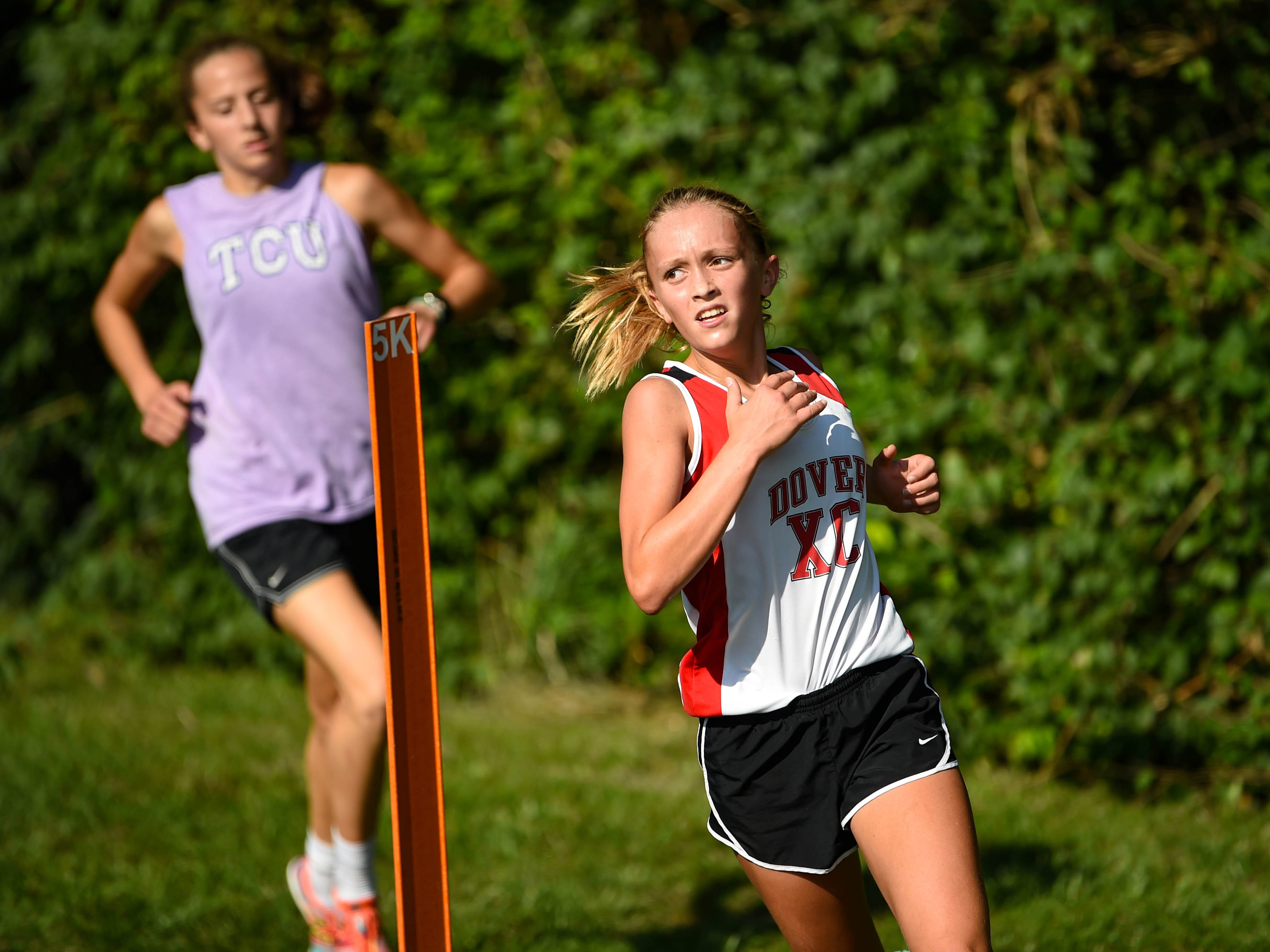 Dover High School rounds the marker during the Cross Country scrimmage at John Rudy County Park on August 30, 2018.