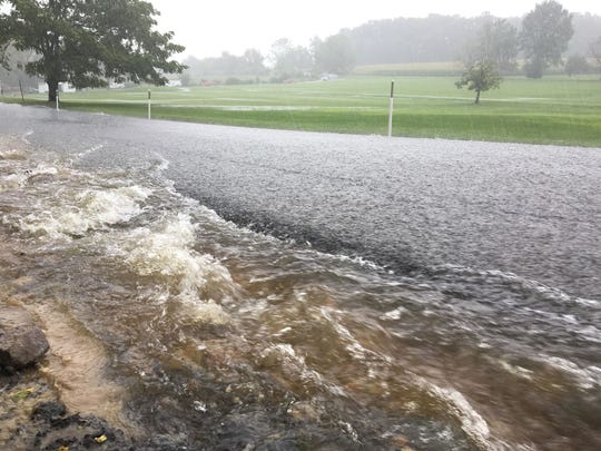 Water runs onto Ore Bank Road in Hellam Township during flash flooding on Friday.
