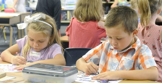 Yerington Elementary School students color in class.