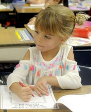 A Yerington Elementary School kindergartner draws a picture of herself on the first day of school.