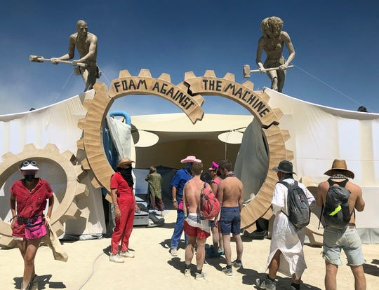 People queue in line at the Foam Against the Machine group foam bath camp on a dusty Thursday afternoon at Burning Man. The foam bath is a large human-sized car wash where people get naked together and hosed down and cleaned.
