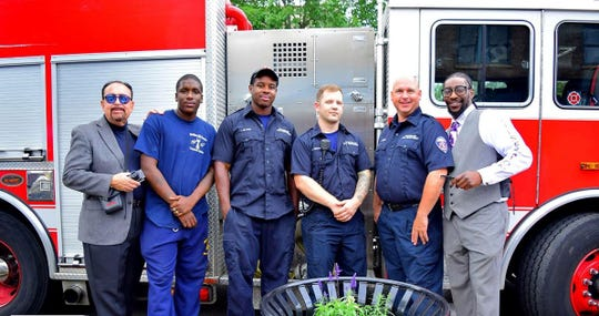 Barber Devon Reynolds Sr., second from left, pictured with firefighters from Rochester Fire Department Engine 10, which offers its help.  Jovan Bradley, far right,  co-owns Brothers and Sisters Unisex Salon with Reynolds.