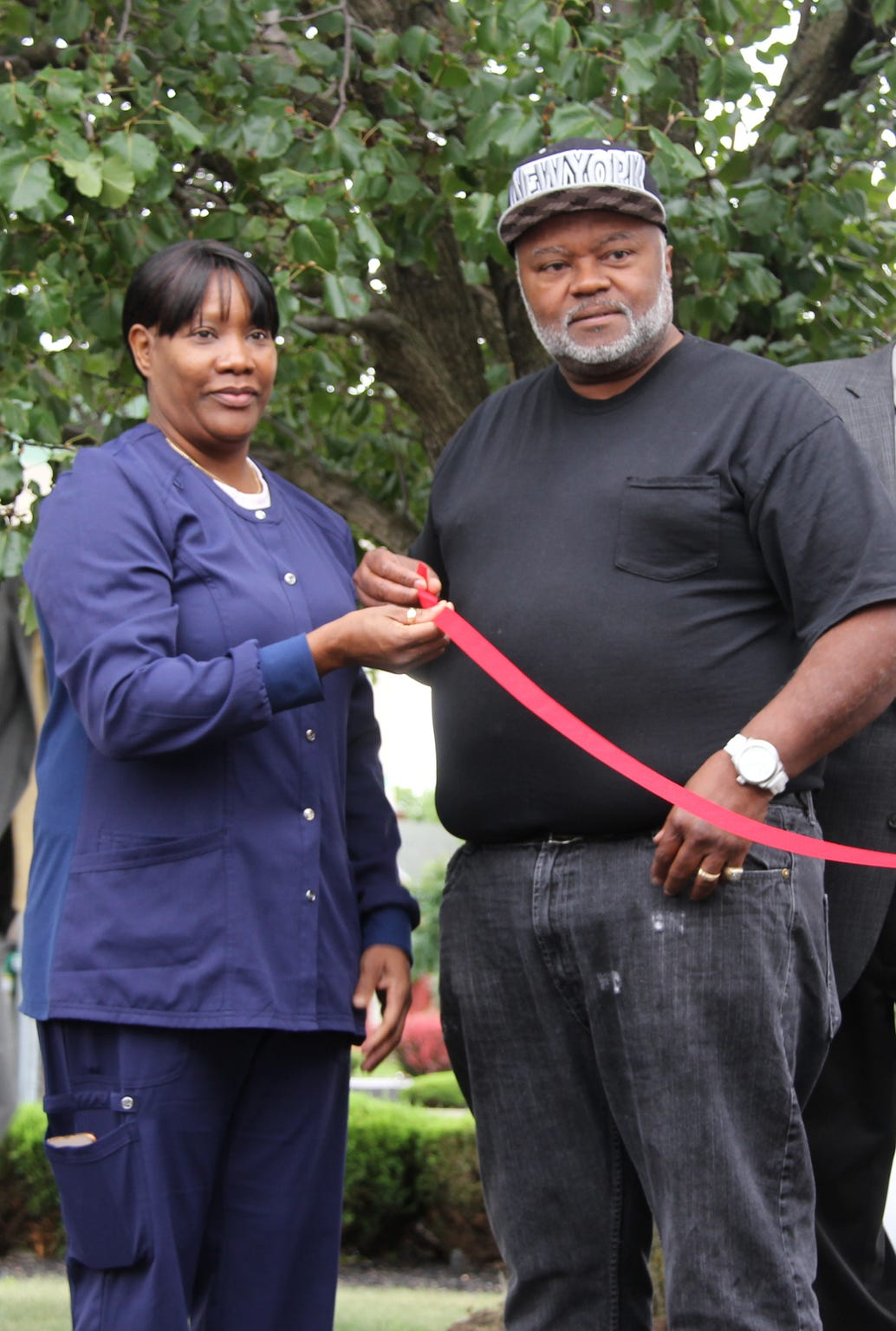 Velma and Kent Handy, aunt and uncle of the late Trevyan Rowe, hold the ribbon during the opening of the Autism Council of Rochester's Autism Family Information & Referral Services Center.