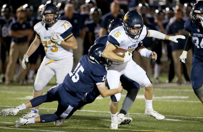 Victor's Sutton Boland is brought down by  Pittsford's Kyle Hennessey during Thursday night's Teddi Bowl at St. John Fisher College.
