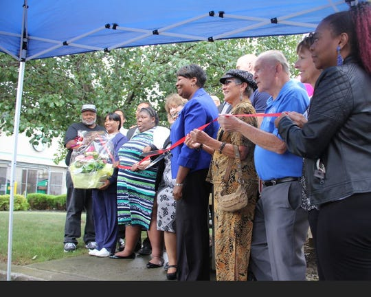 Lawana Jones, executive director of The Autism Council, center in blue, leading the ribbon cutting of the organization's new Autism Family Information & Referral Services Center on Aug. 30 at 2118 Chili Ave. in Gates in the former, vacant Gates Police Department substation. The center is dedicated to the memory of Trevyan Rowe.