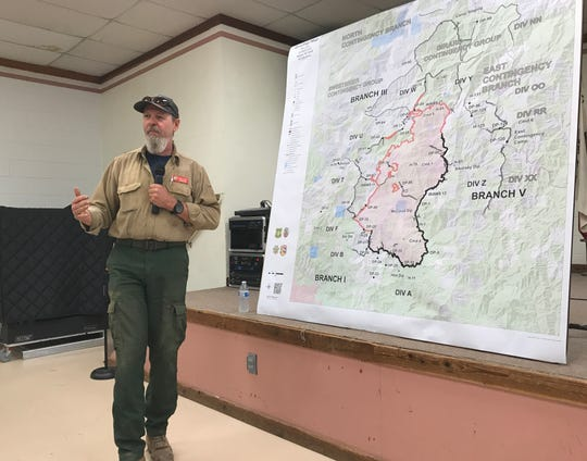 Robin Wills, unified operations chief on the Hirz Fire, speaks to a roomful of people Thursday evening inside the Dunmuir Community Center.