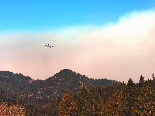 A helicopter takes a bucket of water to the Hirz Fire near Eagles Roost Road off Interstate 5.