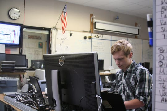 Here, Jonathan Hansen updates some software on a school computer. The tech interns earned about $10.75 an hour while serving the school campuses over the summer break.