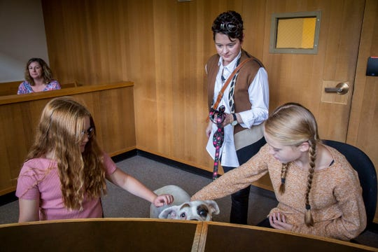 Child volunteers Caris Clarkson, 10, left, and Kelby Clarkson, 13, meet Lilly Mae, center as her trainer Shaney Starr observes in a Marion County juvenile courtroom Tuesday August 28, 2018. The visit was so Lilly Mae could make one more training visit before her official swearing-in ceremony on Sept. 6. The rescued boxer is about to become Oregon's first CASA therapy dog, providing comfort to foster children during court proceedings. Lilly Mae was rescued and trained by CASA executive director Shaney Starr. The child volunteers played the role of kids who would be attending a juvenile court proceeding so Lilly Mae could learn the surroundings and process of going to court in a support capacity.