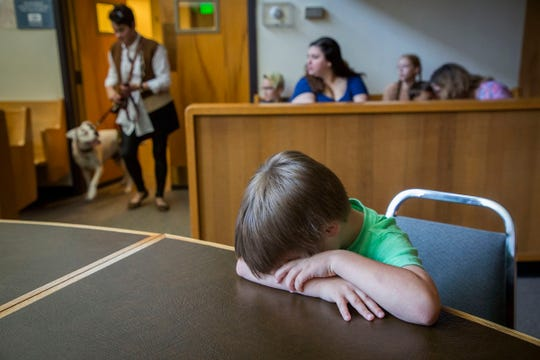 As child volunteer Gideon Stevenson, 5,  sits with his head down on a table, Shaney Starr, right, leads Lilly Mae into a Marion County juvenile courtroom Tuesday August 28, 2018,  as she makes one more training visit before her official swearing-in ceremony on Sept. 6. The rescued boxer is about to become Oregon's first CASA therapy dog, providing comfort to foster children during court proceedings. Lilly Mae was rescued and trained by CASA executive director Shaney Starr. The child volunteers played the role of kids who would be attending a juvenile court proceeding so Lilly Mae could learn the surroundings and process of going to court in a support capacity.