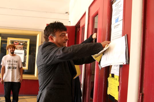 Fox Theater Owner Anthony Lane tears closure notices off the theater door on Thursday.