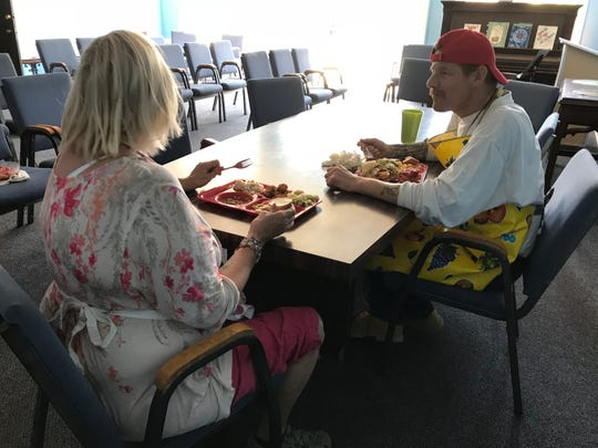 Derek Vasselin and Mary Gillies, both volunteers in First United Methodist Church's kitchen, eat lunch after meals have been served.