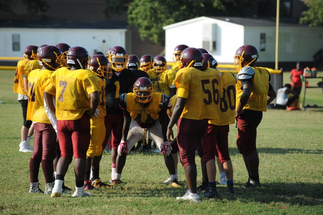 Keionte Nutter (center) waits commands the defense during a huddle during a Washington High School football practice.